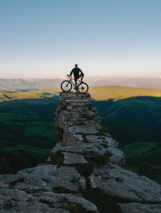 Man with a bicycle on a cliff