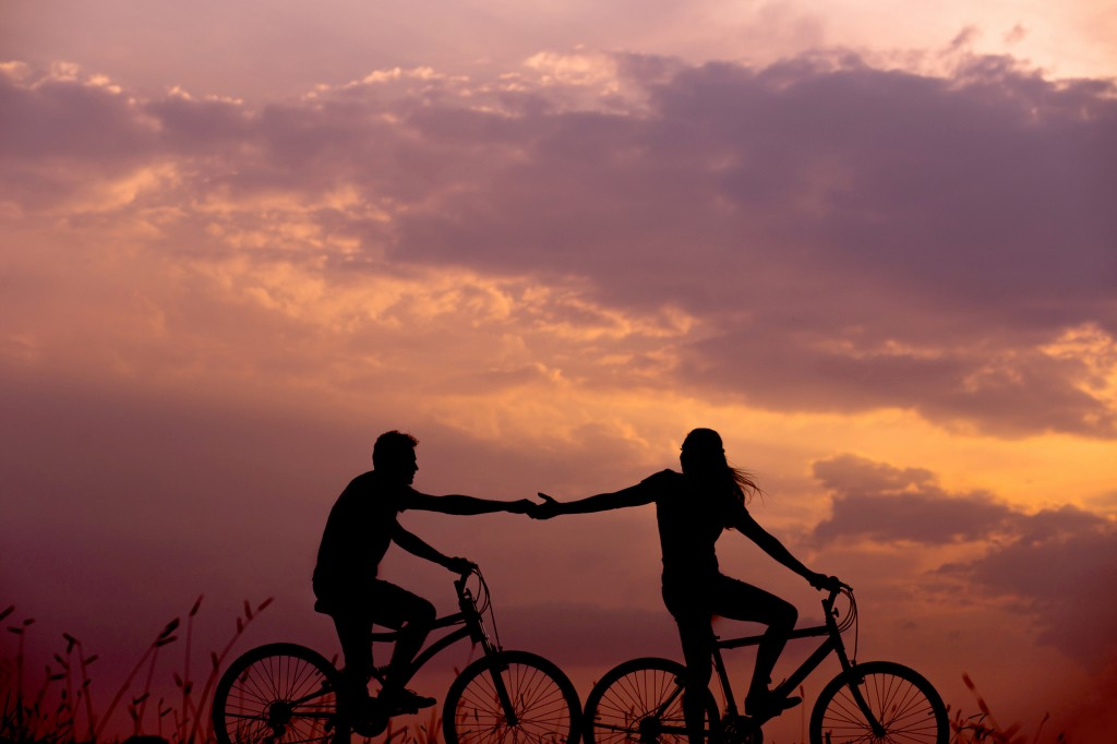 Two bike riders supporting one another